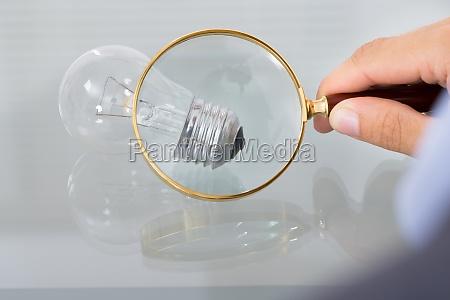 businessman inspecting lightbulb