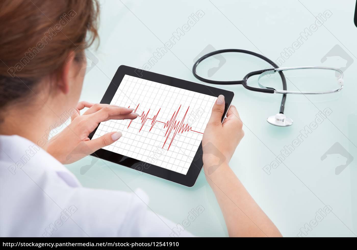 doctor, using, tablet, computer, at, desk - 12541910