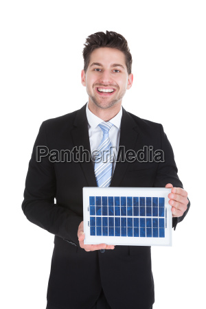 smiling businessman holding solar panel