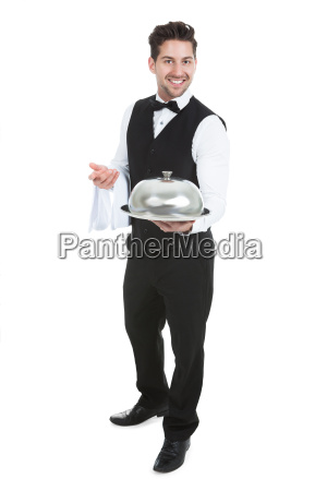 confident waiter holding domed tray