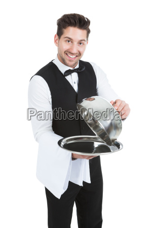 butler lifting cloche from serving tray