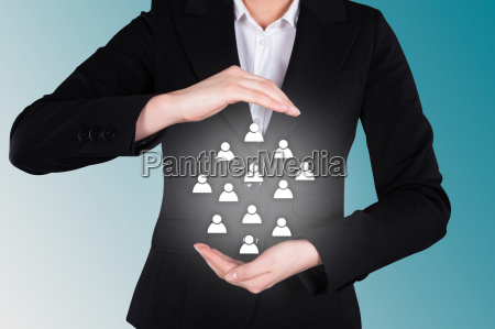 businesswoman protecting human icons representing leadership