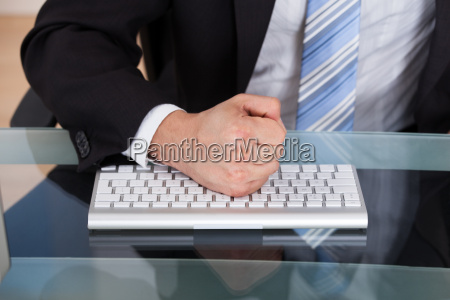 midsection of businessman pounding fist on