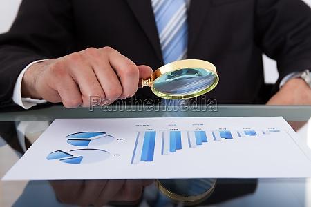 businessman analyzing bar graph through magnifying