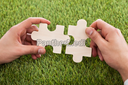 hands connecting two puzzle pieces