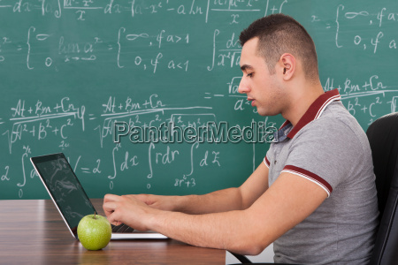 student solving maths problem on laptop