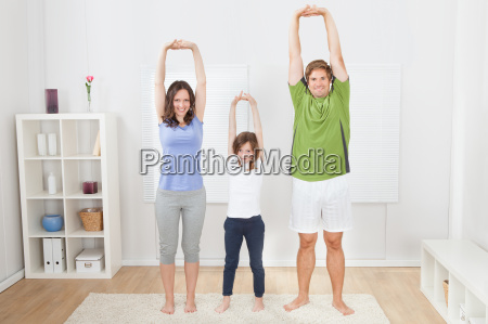 portrait of fit family performing yoga