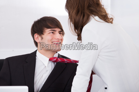 businesswoman pulling male colleagues tie while