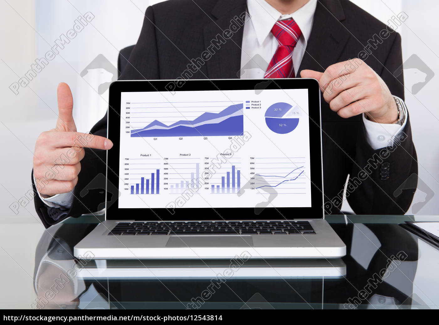 confident, businessman, displaying, laptop, at, desk - 12543814