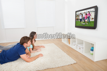 family, watching, tv, at, home - 12543540