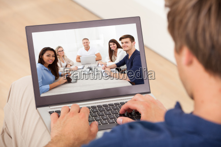 man attending conference meeting on laptop