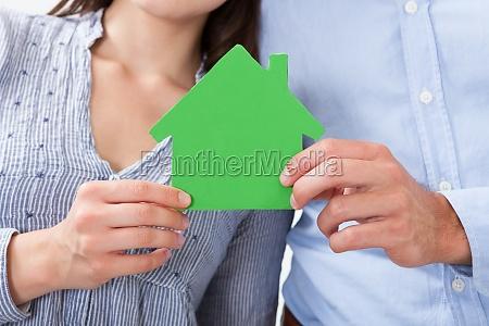 couple holding green house model
