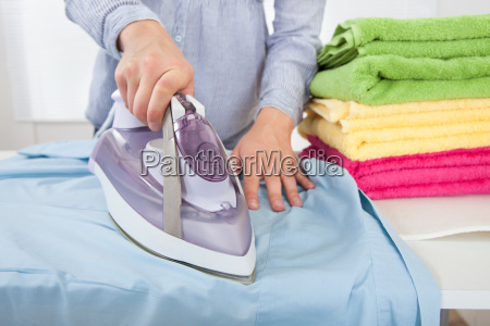midsection of woman ironing shirt