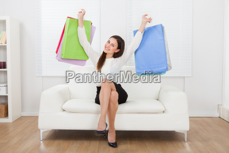 excited businesswoman holding shopping bags on