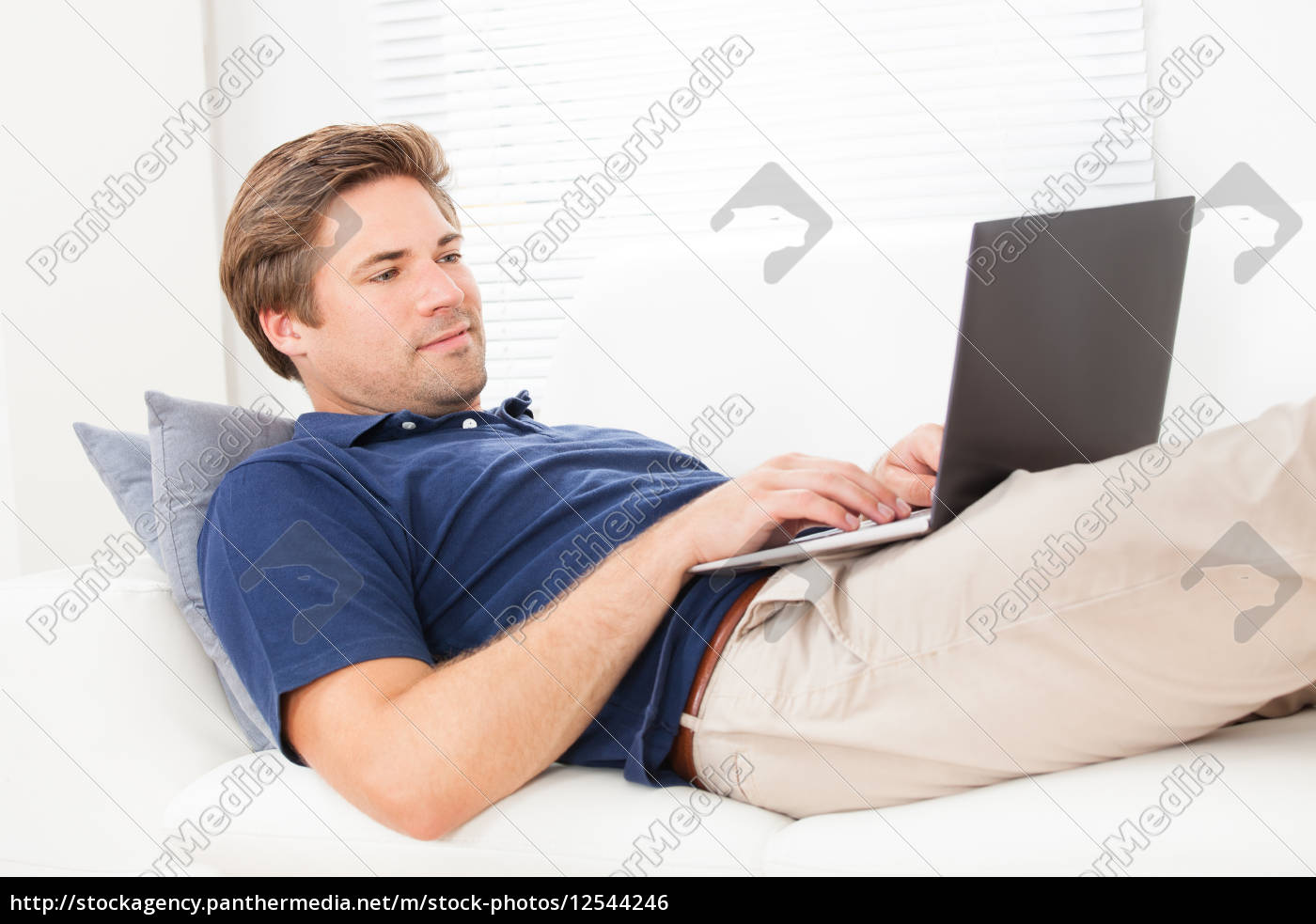man, using, laptop, on, sofa, at - 12544246