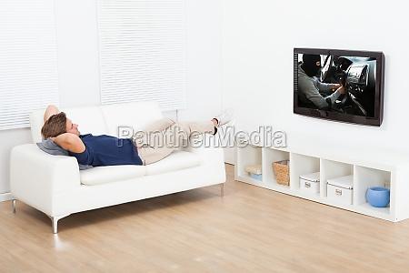 man, watching, tv, while, lying, on - 12544262