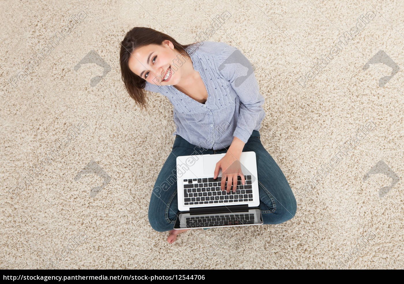 young, woman, using, laptop, on, rug - 12544706
