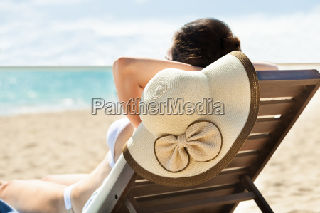 woman with sunhat relaxing on deck