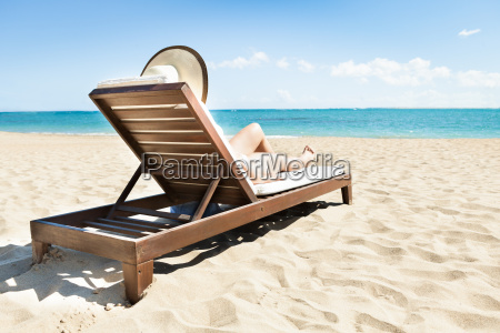 woman sunbathing on deck chair at