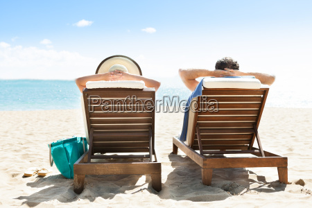 couple, relaxing, on, deck, chairs, at - 12545950