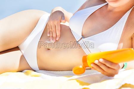 woman in bikini applying sunscreen while