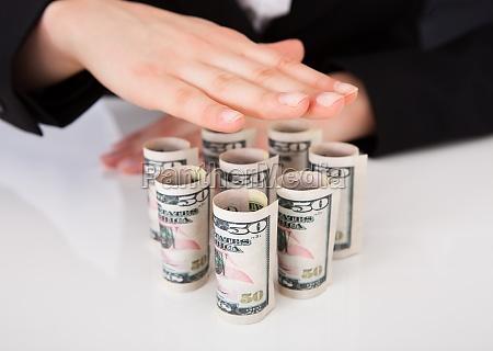 businesswoman shielding rolled dollar bills