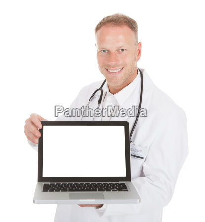 smiling young male doctor displaying laptop