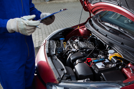 mechanic holding clipboard in front of