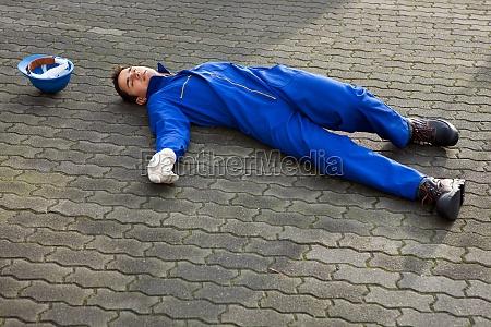 unconscious repairman in uniform lying on