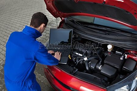 mechanic using laptop while repairing car