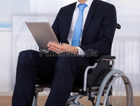 businessman using digital tablet on wheelchair