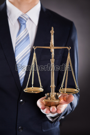 businessman holding justice scale