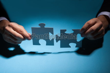 businessman joining puzzle pieces at desk