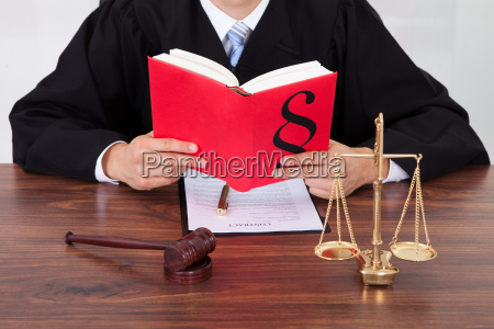 judge reading book at table in
