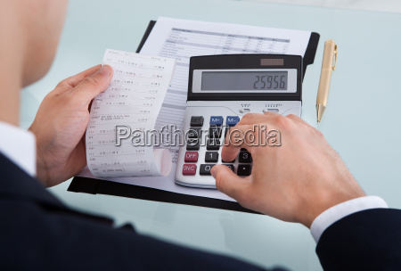 businessman holding receipt while calculating expense