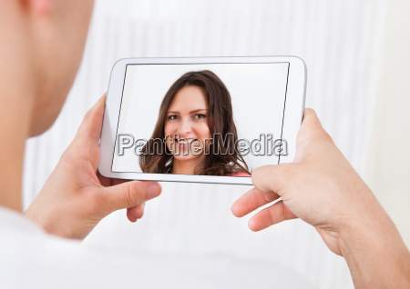 man video conferencing with woman on