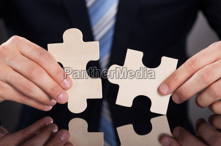 businessman, joining, puzzle, pieces, at, desk - 12551560