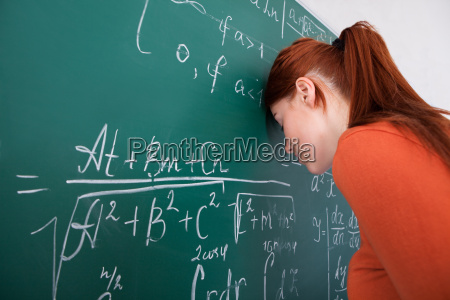 student, leaning, head, on, blackboard, in - 12552510
