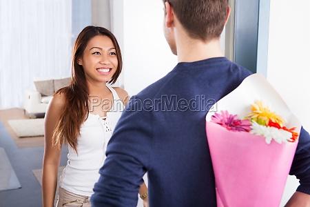 man hiding bouquet from woman