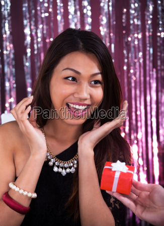 surprised woman receiving gift in restaurant