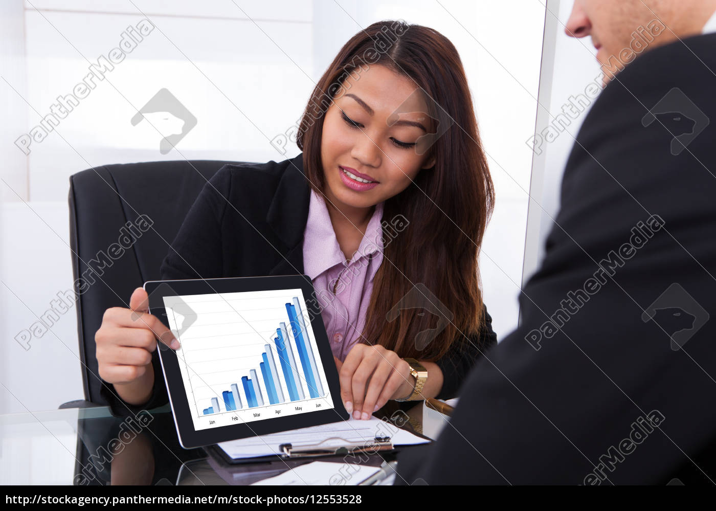 businesswoman, showing, digital, tablet, to, colleague - 12553528