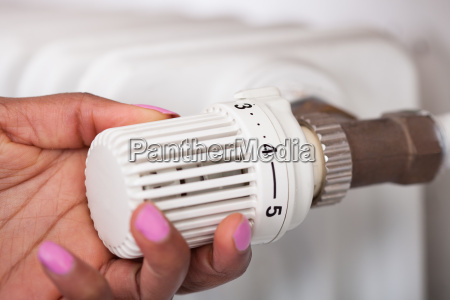 woman, adjusting, thermostat - 12553208