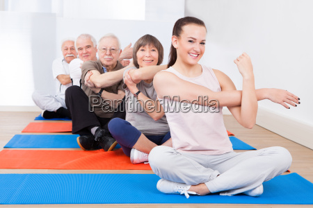 trainer and senior customers exercising