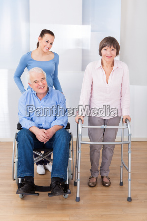 disabled senior couple with caregiver