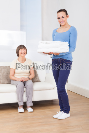 caretaker carrying towels with senior woman