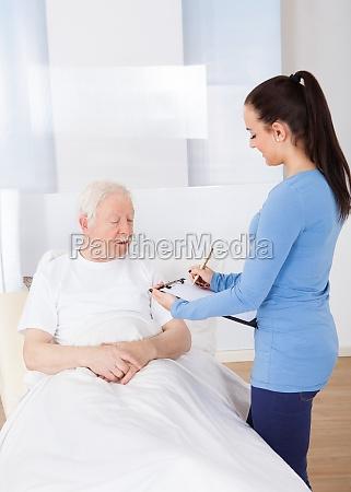 caretaker with clipboard attending senior patient