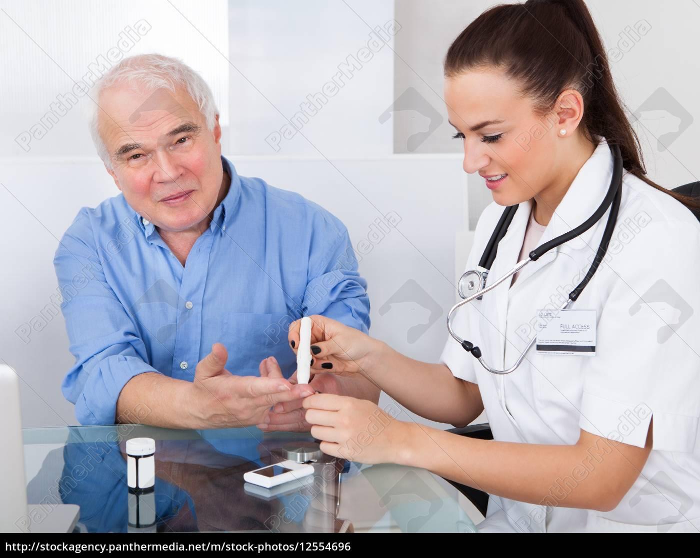 doctor, using, lancelet, on, senior, man - 12554696