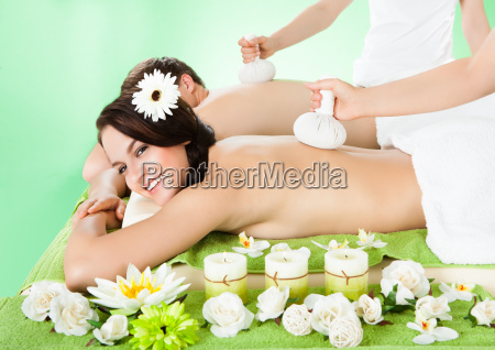 couple receiving massage with herbal compress