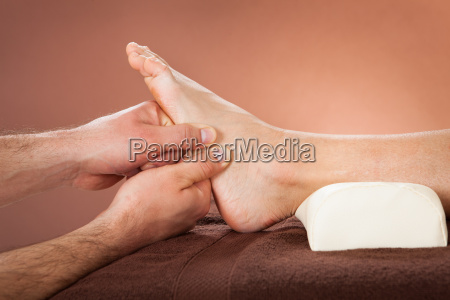 therapist giving foot massage to female