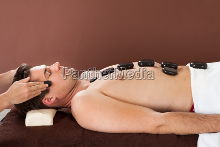 man receiving hot stone therapy in